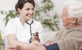 female medical staff checking blood pressure of senior man