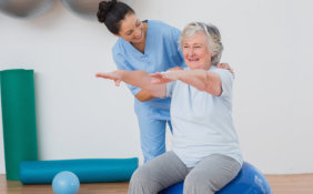 caregiver assisting senior woman in her exercise