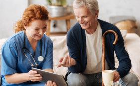 female medical staff with senior man watching something on tablet