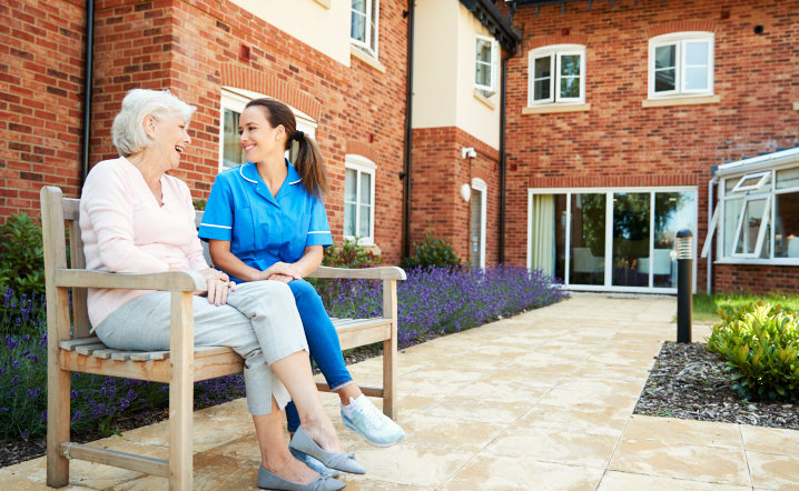 senior woman with female caregiver smiling while sitting on bench
