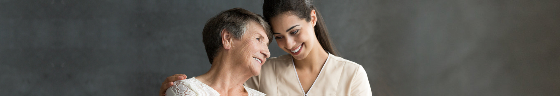 senior woman and caregiver smiling