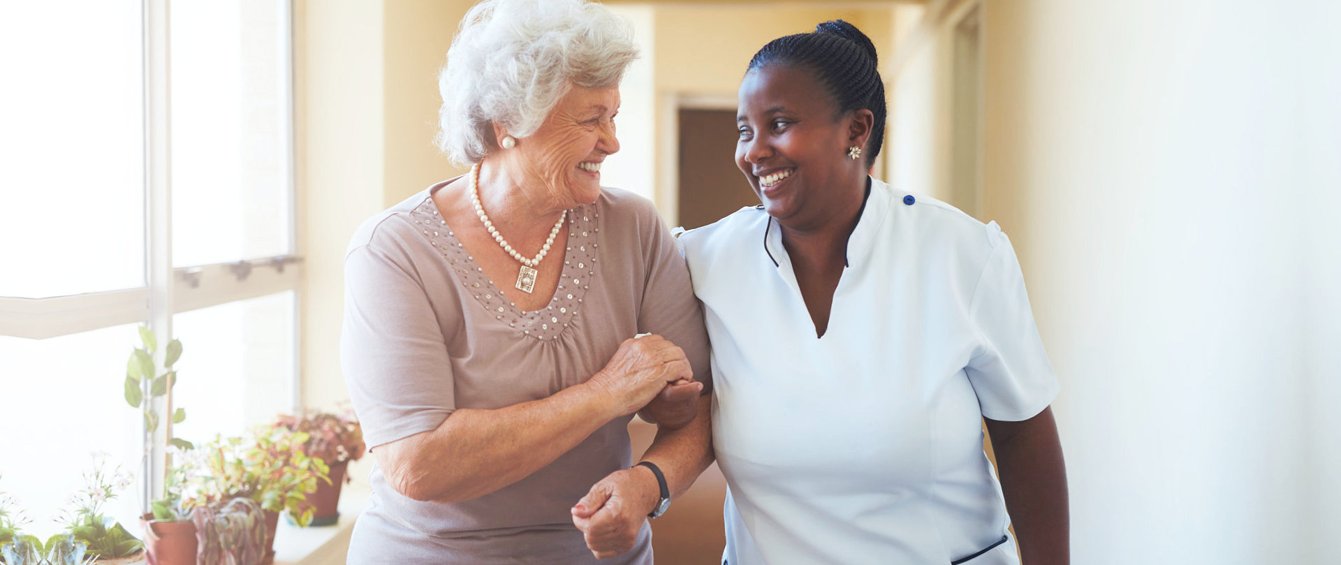 senior woman with caregiver smiling at each other
