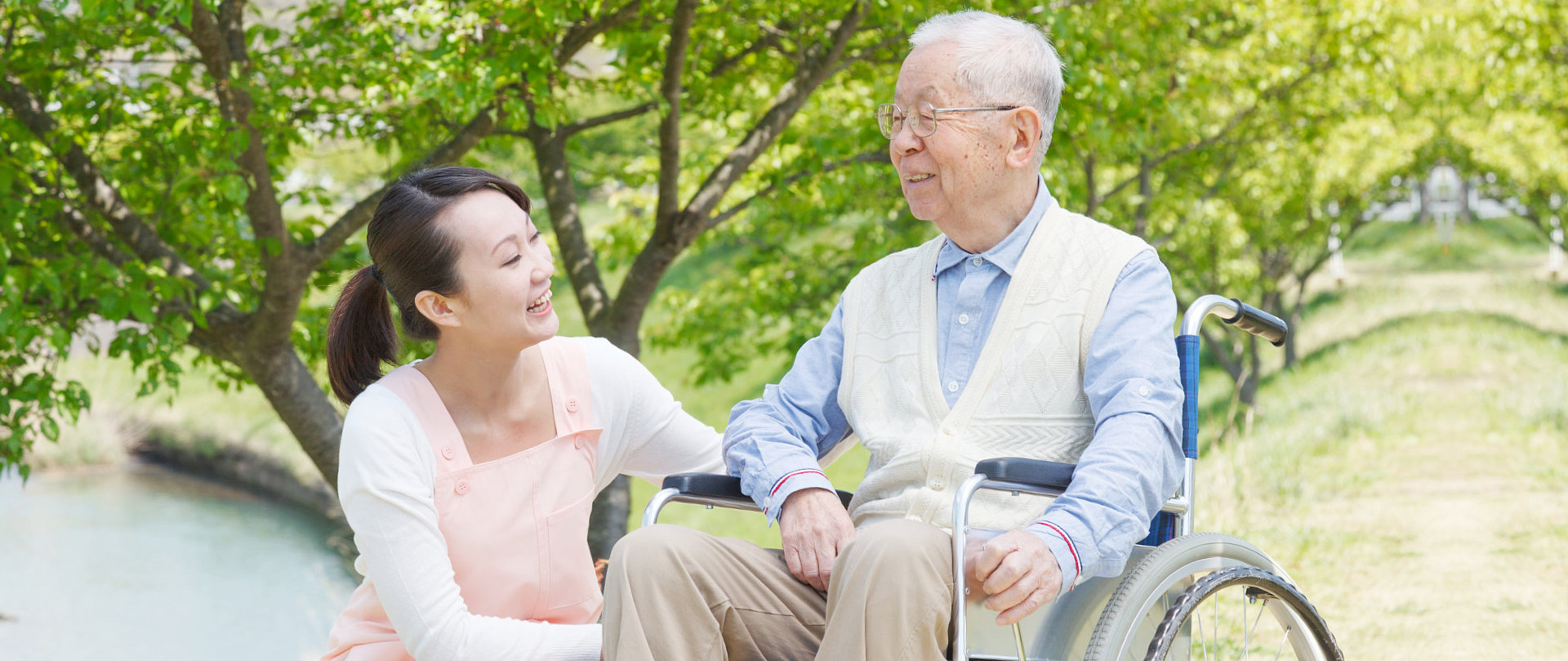 female caregiver with senior man on wheelchair smiling