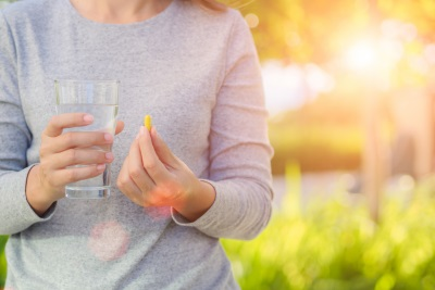 woman holding a glass of water and a medicine pill