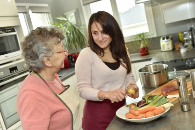 young woman preparing food for an elderly woman