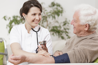 young nurse taking blood pressure of an elder man