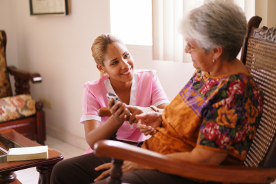 caregiver assisting a senior woman in a rocking chair