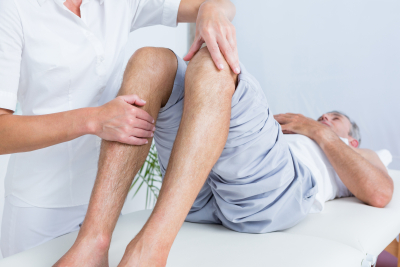 therapist massaging a man's knee