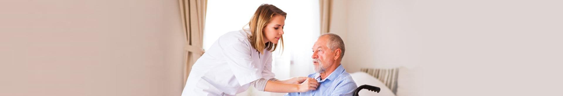 caregiver assisting senior man on bed